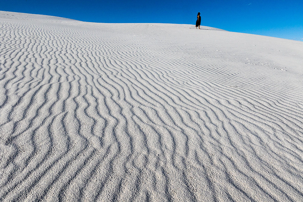 Gypsum sand dune with woman in black